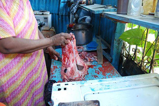 アメリカに滞在する娘にお土産用の「雄牛の頭の煮込み」を料理する母。ドミニカ共和国、バニ。