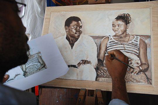 アーティスト、パパケイの描くポピシとモミシ(ナイジェリア英語で、「父さんと母さん」の意)の肖像画。ラゴスの写真館で1976年に撮った、結婚してまもないころのふたりの写真を貸りて、それをもとに、パパケイに油彩で描いてもらった。ナイジェリアでは、アーティストに依頼して、肖像写真を肖像画にしてもらい、居間に飾ることがしばしば好まれる。贈りものとしても、価値の高いものとして喜ばれる。2010年7月22日、イフェ、モーレ地区のパパケイのアトリエにて。