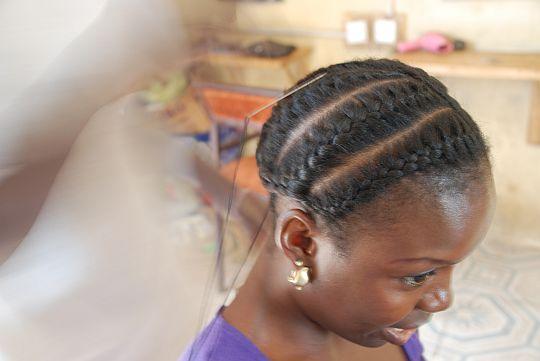 美容師はトインの自毛をすべて編みこみ、これから、針(頭部の頂点付近、編みこまれた髪に刺してある白っぽい線)と黒い糸(針から垂れている黒い線)でその自毛につけ毛を縫いつけていく