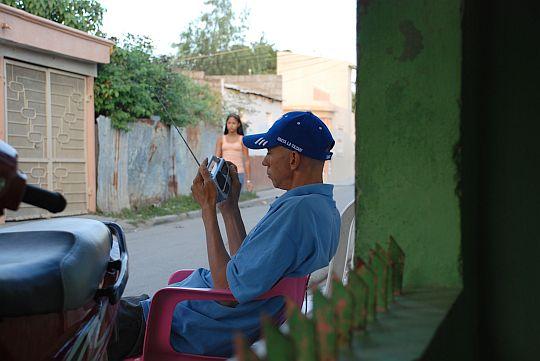 ラジオの野球中継を聴くロヘリオ。ドミニカ共和国、バニにて