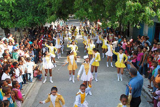 パトロナレスを前にバリオを行進する学生のバトン隊。ドミニカ共和国、バニにて